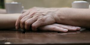 An older woman grasps the hands of a younger woman