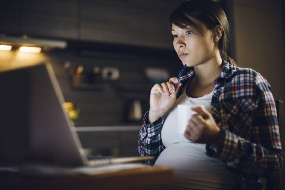 Pregnant woman thoughtfully looks at a computer while holding a white coffee cup