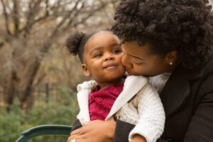 Post-pregnancy care for birth moms, Dark-skinned mom kisses the cheek of her toddler daughter