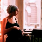 Pregnant mom sits in window nook and thoughtfully looks out the window.