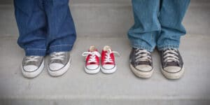 Two adult grey sneakers frame a small red pair of empty sneakers.