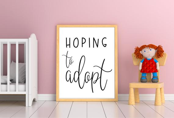 """A crib, chair, and doll frame a whiteboard with """"Hoping to Adopt"""" written on it."""