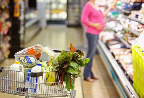 Pregnant mom chooses healthy items in the grocery store.