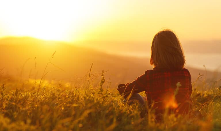 Woman wearing a plaid shirt sits in a field looking toward the sunset