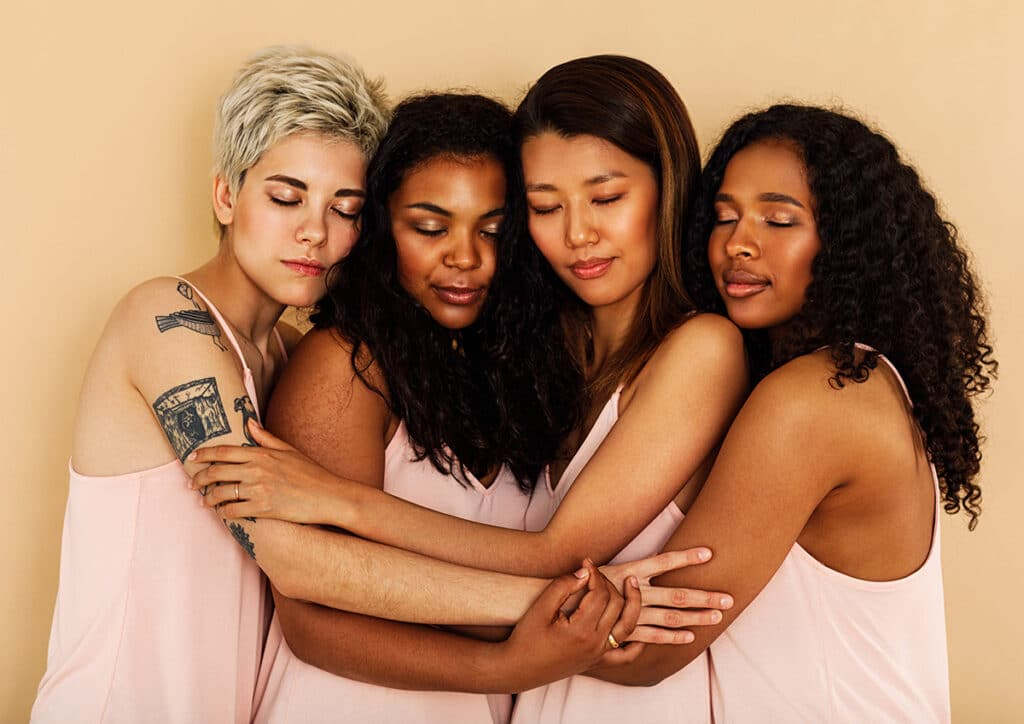 group of diverse women hug